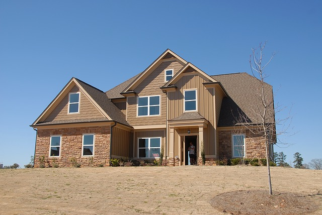 Large two-story home with tan and brick exterior.