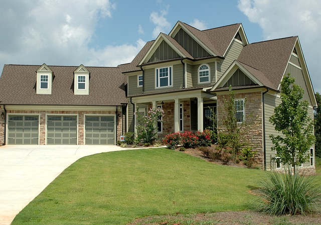 Large multi-level home with olive green stucco exterior, a wide driveway, and three-car garage.