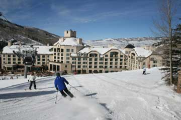 A skier coming to a stop in front of a large resort hotel in Beaver Creek.