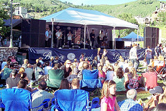 A small concert stage surrounded by people sitting in lawn chairs.