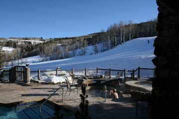 View of Bachelor Gulch's ski slopes and Avon mountains from the deck of a swimming pool.