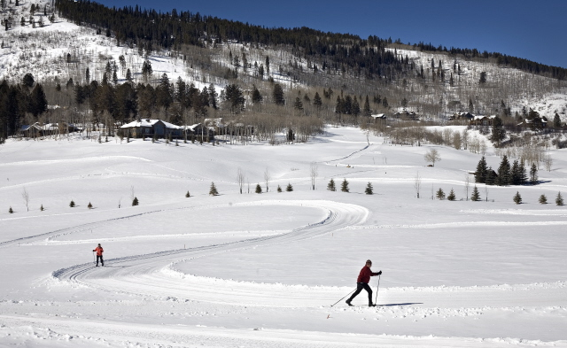 Two people skiing along fresh white powder on a snowy mountain in Vail Valley.