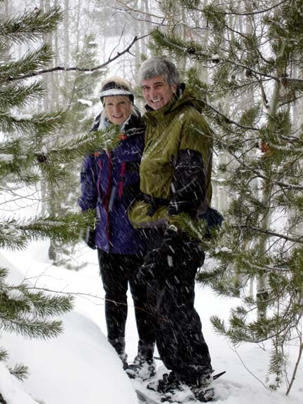 A man and a woman standing between evergreen trees on a snowshoe trail.