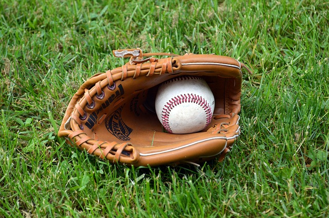 A baseball nestled in a leather glove sitting on a grassy field.