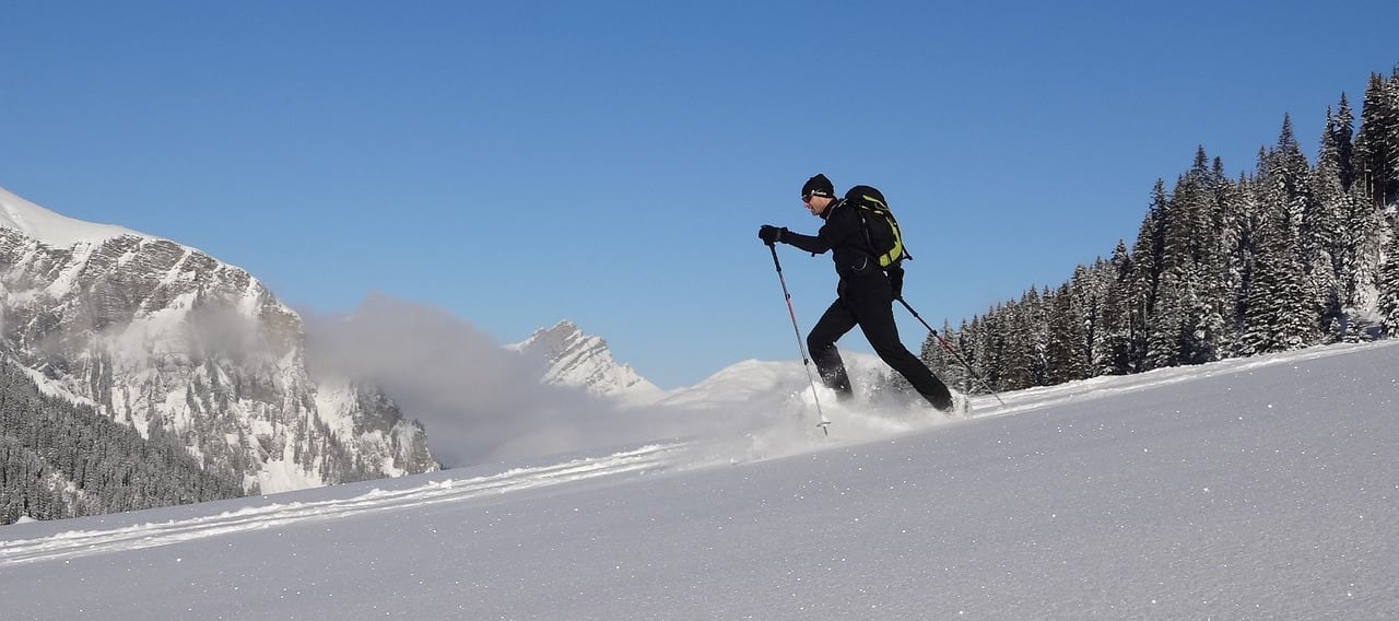 A man wearing snowshoes hiking down a snow-covered mountainside.