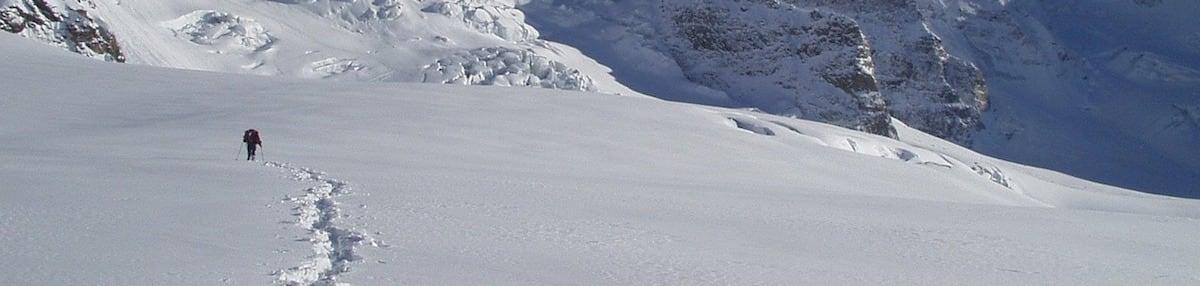 A lone hiker trekking through the snow up a mountain.