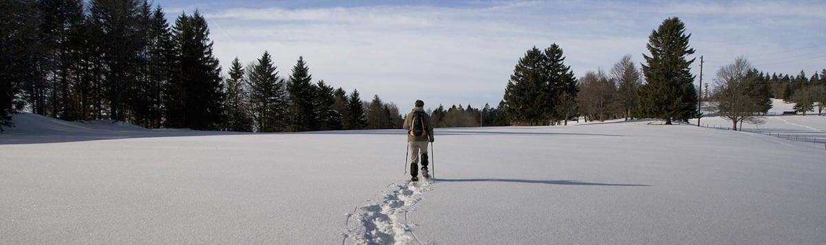A person snowshoeing along fresh powder.