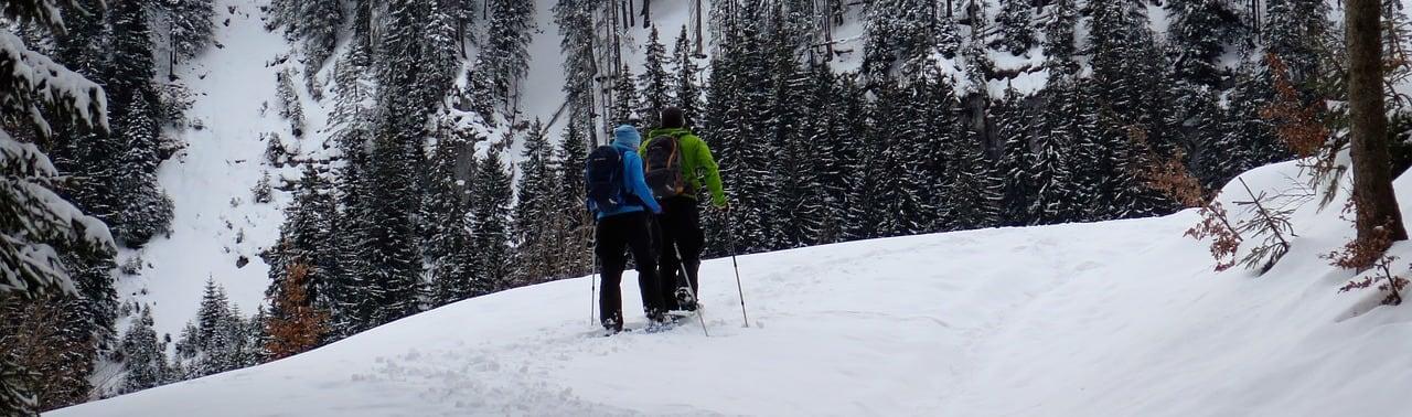 A couple hiking along a snow-covered mountain ridge.
