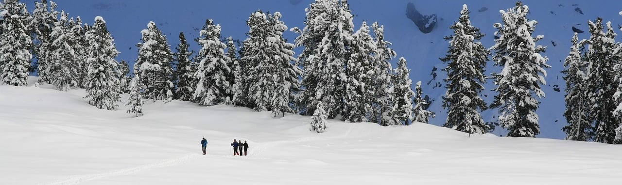 A group of three people hiking over snow on a mountain.
