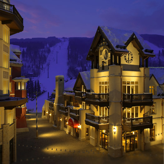 A luxury hotel on a snow-covered street at night in Vail Village.