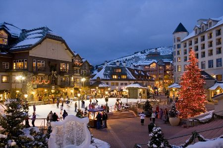 A twilight view of a ski village lit with an ice rink in the middle.