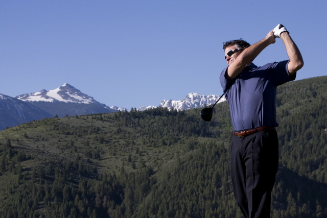 A golfer in a blue polo shirt teeing off at a golf course with mountain ranges in the background.