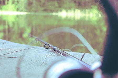 A fishing pole resting on a wooden dock overlooking a creek.