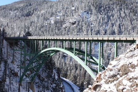 A steel arch bridge connecting two ragged mountains in Red Cliff, CO.
