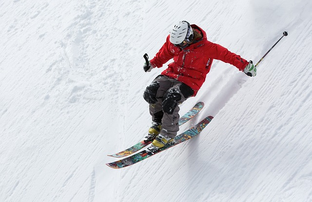 A person wearing a red jacket and skiing down a steep mountainside.