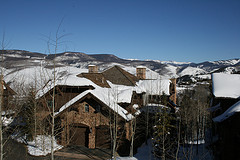 Snow-covered roofs on mountain lodge-style houses with mountains in the background.