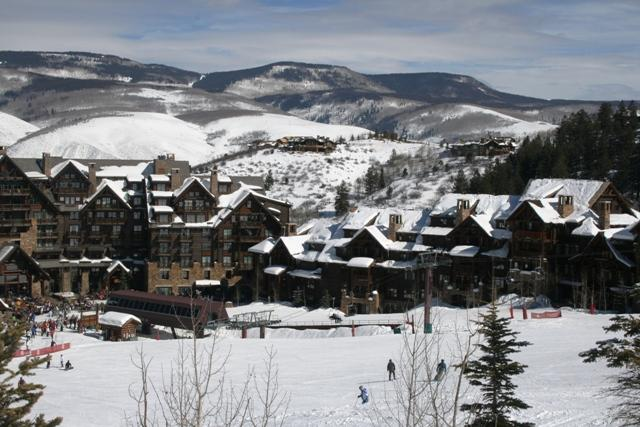 View of Snow Cloud mountain villa-style condo with snow on the ski slopes and on the mountains in the background.