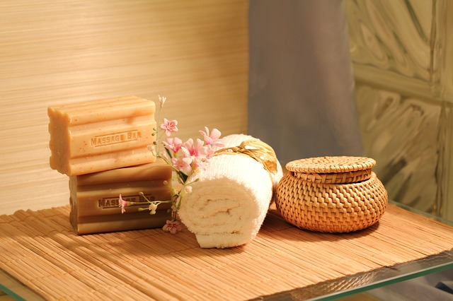 A bar of soap, rolled towel, and wicker basket sitting on a wooden table in a spa room.