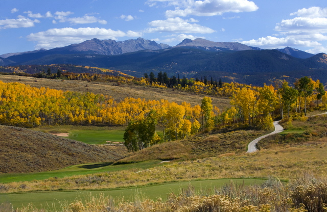 A golf course on rolling hills overlooking a mountain range in Edwards, CO.