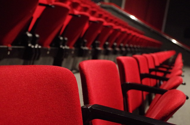 A row of empty red theater seats facing a stage.