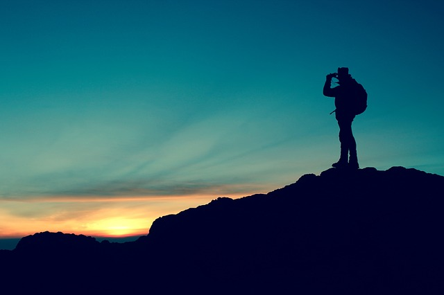 A hiker standing on a mountainside and looking through binoculars.