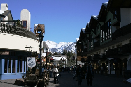 A bustling street lined with shops and restaurants with Gore Range in the background.