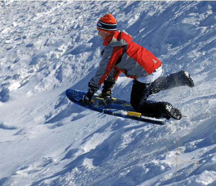 A child wearing a red coat and sledding on a snowy hill.