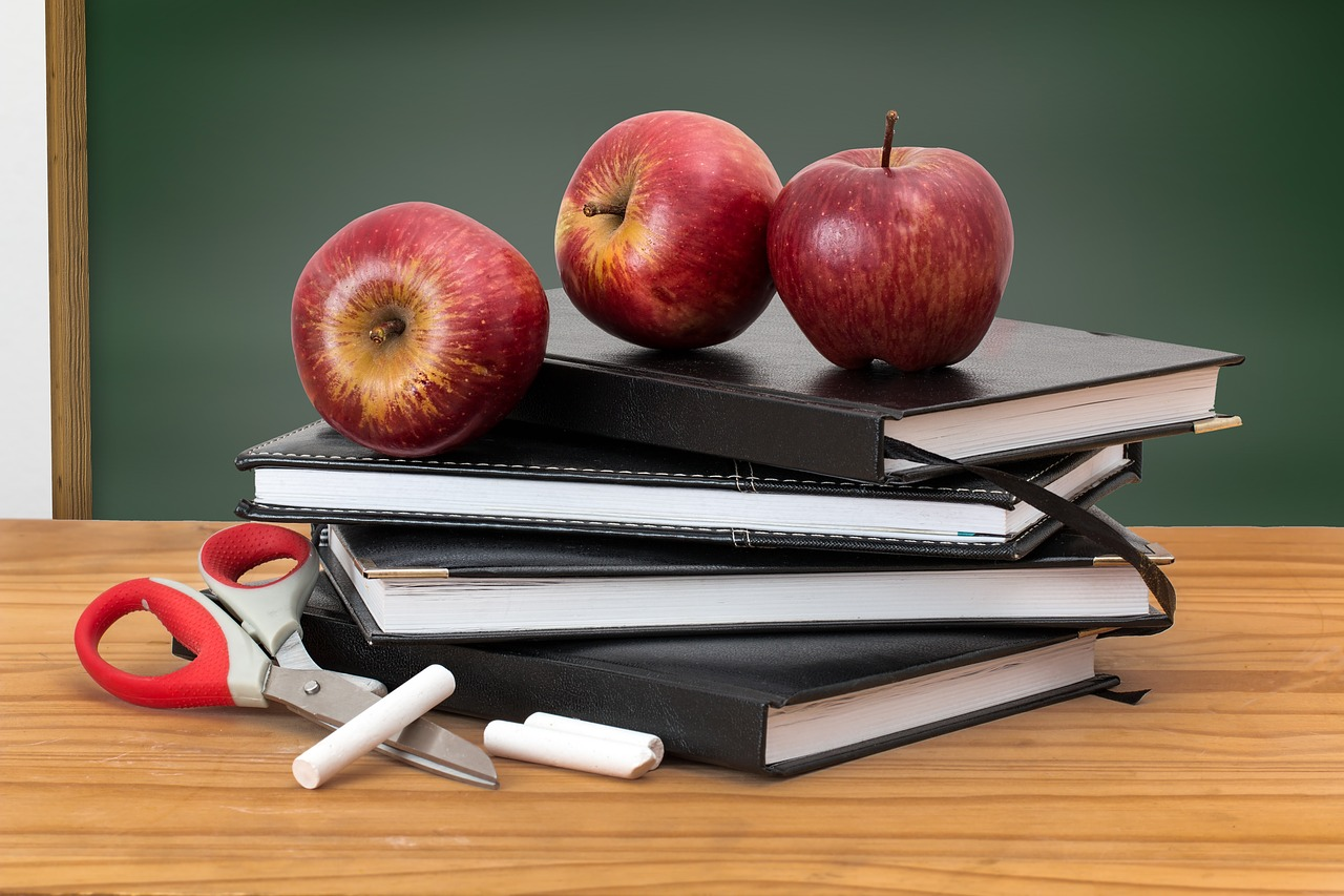 stack of black notebooks on a desk with scissors red apples and chalk with green chalkboard behind it