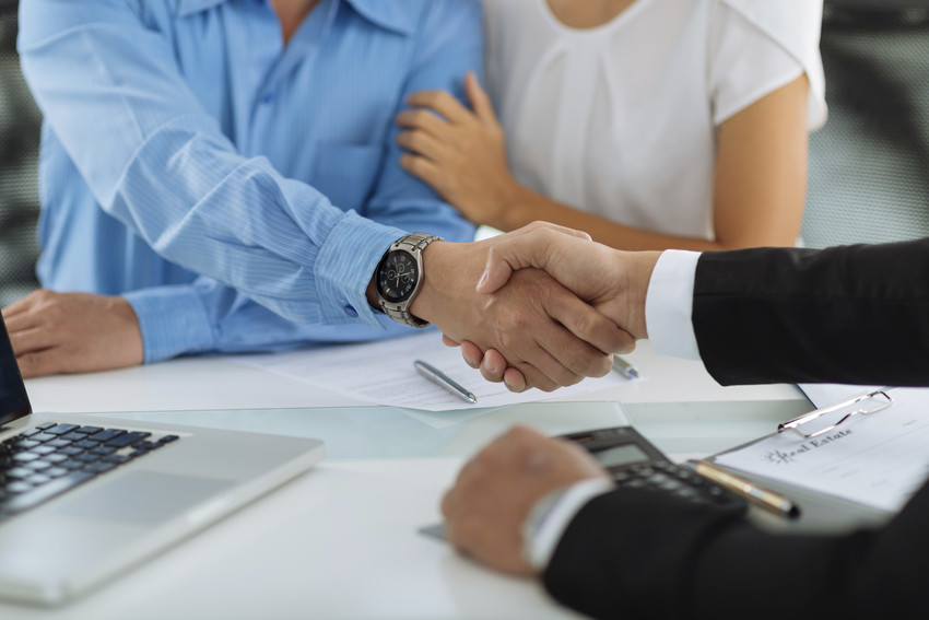 real estate agent and buyers shaking hands